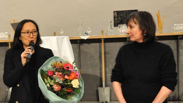 Eine Frau mit Blumenstrauss, in ein Mikrofon sprechend, neben ihr eine zweite Frau, ebenfalls stehend.
