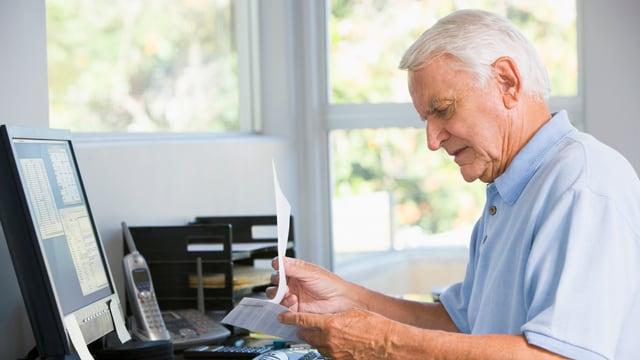 Ein Mann vor einem Computer studiert einen Brief