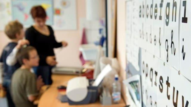 Lehrerin im Klassenzimmer vor der Wandtafel mit Schülern.