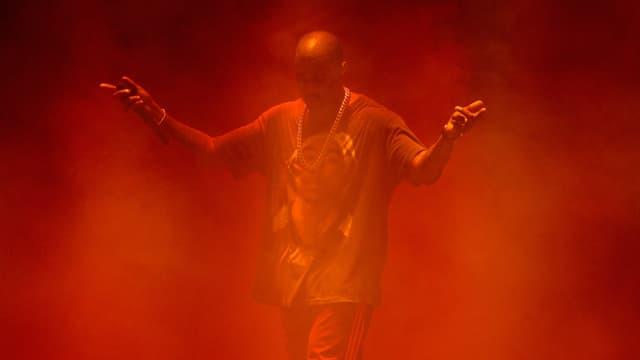 Kanye West mit erhobenen Händen auf einer vernebelten Bühne