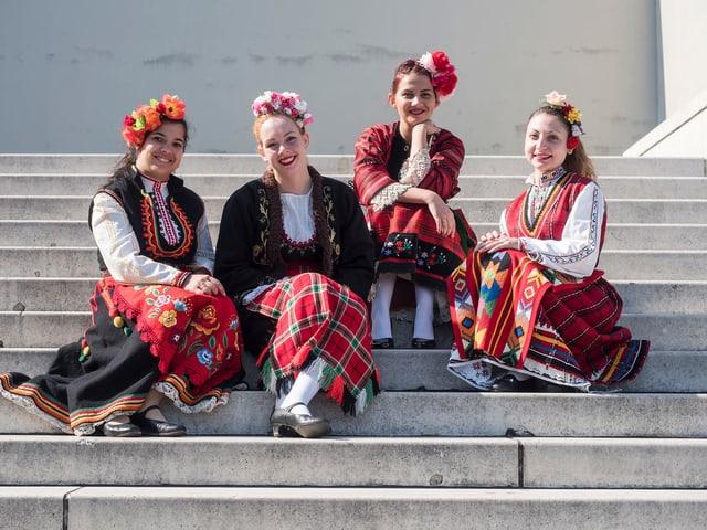 Vier Sängerinnen in ihrer Landestracht sitzen auf einer Steintreppe.