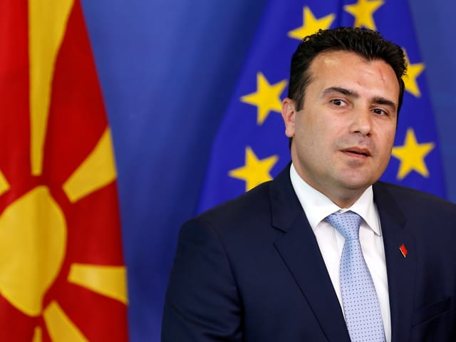 Zaev steht von einer mazedonischen und einer europäischen Flagge