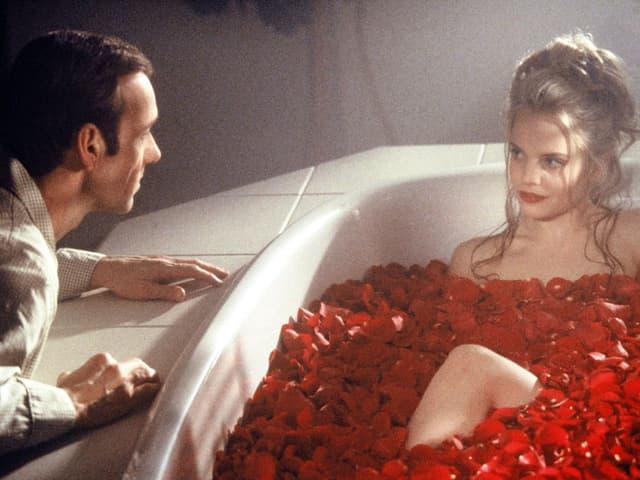 Lester lehnt sich an den Rand der Badewanne, in der sich Angela in Rosenblättern räkelt.