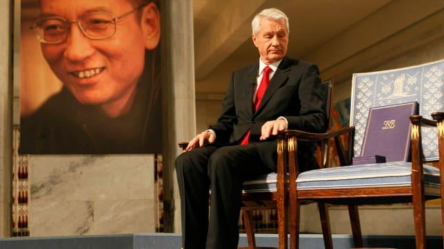 Ein Mann sitzt auf einem Stuhl, der Stuhl nebendran ist leer, auf der anderen Seite eine grosse Fotografie von Liu.