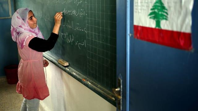 Ein Mädchen mit Kopftuch schreibt etwas an die Wandtafel