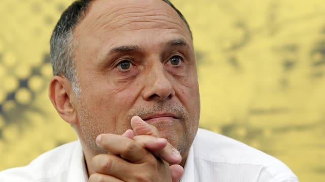 Der Regisseur Christoph Schaub in weissem Hemd vor einem gelben Hintergrund.