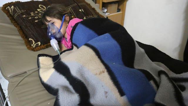 Kind mit Sauerstoff-Maske unter Decken.