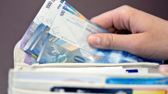 Hand greift ins Portemonnaie und zieht Banknoten raus.