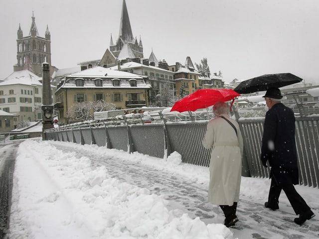Ein Paar läuft in Lausanne über eine schneebedeckte Brücke.