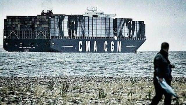 Ein Mann steht am Strand, im Hintergrund ist ein Containerschiff zu sehen, auf ein Bild riesiger Augen geklebt ist.