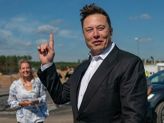 Musk streckt den Zeigefinger der rechten Hand in die Höhe und lächelt siegessicher.