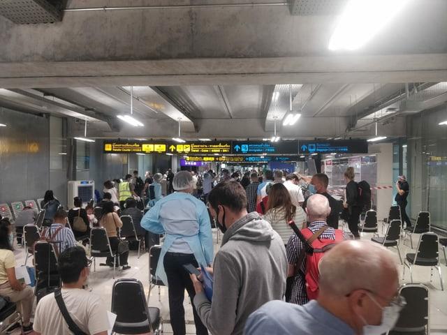 Im Bild wartende Reisende, die vom Gesundheitspersonal getestet werden.