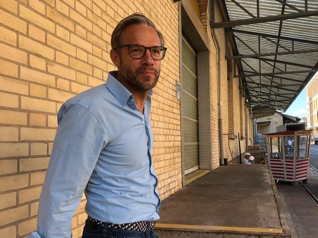 Ein Mann in hellblauem Hemd schaut in die Kamera. Er steht vor einer Backsteinmauer.