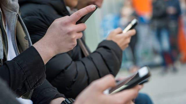 Hände von Jugendlichen, die ein Smartphone halten und mit dem Daumen bedienen.