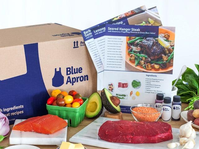 """Tisch mit rohen Fleisch, Gemüse. Im Hintergrund ein Rezept und eine Schachtel mit der Aufschrift """"Blue Apron"""""""
