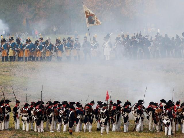 Französische Truppen stehen den Alliierten auf einem Feld gegenüber, über ihnen steigen Rauchwolken auf.