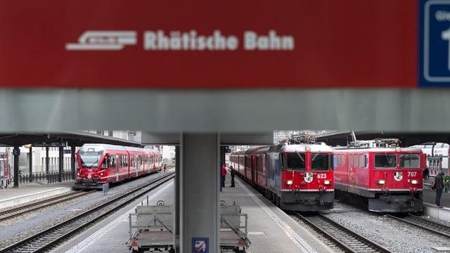 Züge hinter Schild mit Schrift Rhätische Bahn