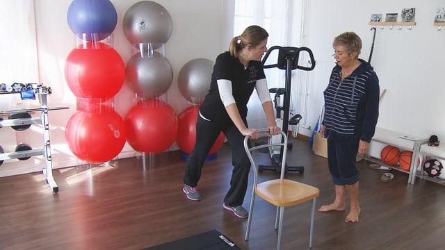 Eine Physiotherapeutin zeigt einer Patientin die Übung gegen Wadenkrämpfe.