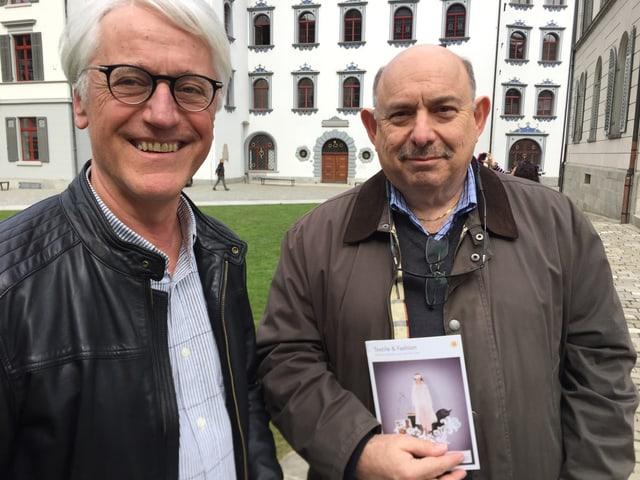 Rolf Schmitter, Präsident Textilland Ostschweiz und ein US-Tourist vor dem Textilweg auf dem Klosterplatz.