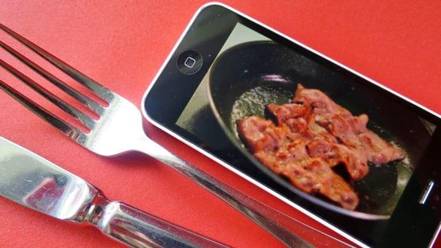 Messer und Gabel und ein Handy, auf dem man einen Speck sieht.