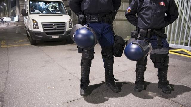 Zwei Polizisten stehen in Schutzmontur vor einem Polizeiauto.