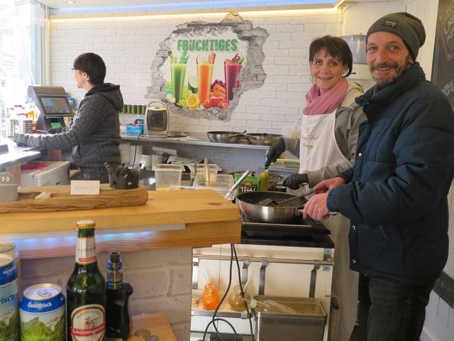 Leute bereiten Essen vor, das bei der Rondelle gekauft werden kann.