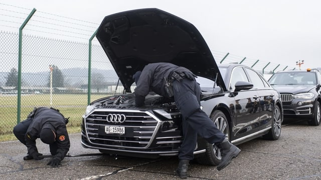 Ein Polizist beugt sich über eine geöffnete Motorhaube, eine zweiter hält mit einer Stange eine Kamera unter das Auto