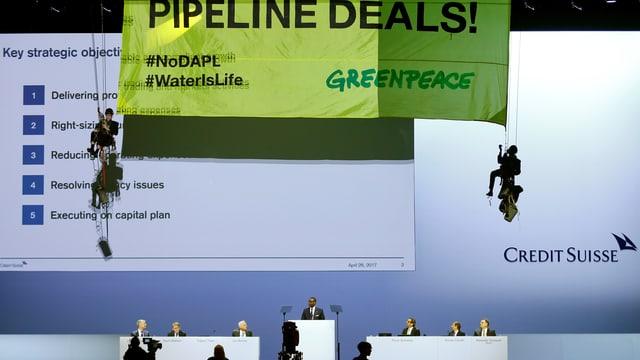 Podest mit CS-Chefs. Darüber hängen Aktivisten an einem Plakat gegen Pipelines.