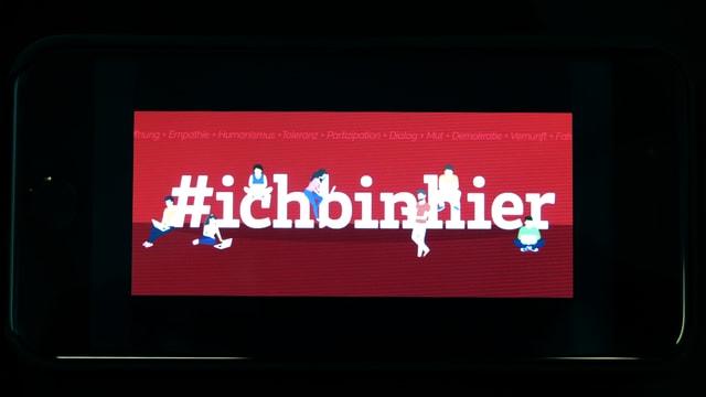 Smartphone mit Titelbild des Facebook-Accounts. Darauf Schriftzug «#ichbinhier».