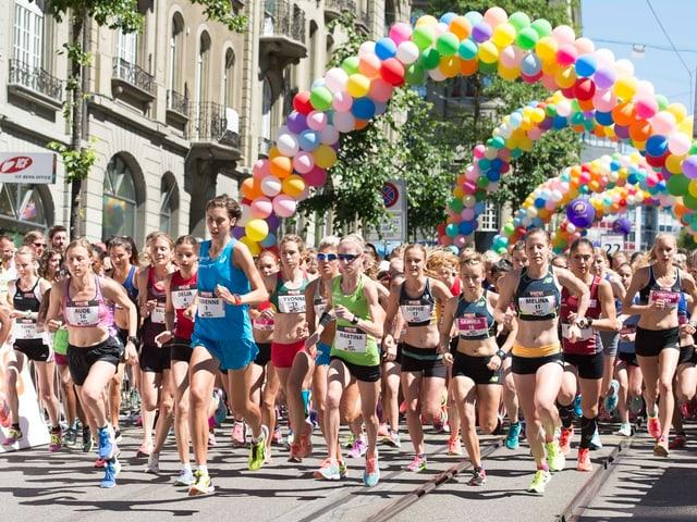 Frauen rennen durch von Ballons gesäumte Strassen der Stadt Bern.