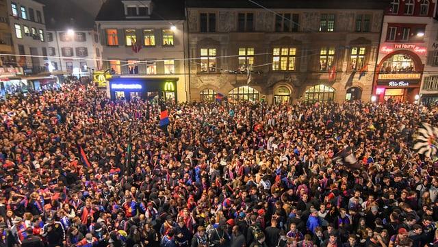 Man sieht hunderte von FCB-Fan auf dem Barfüsserplatz. Es ist Nacht und man sieht die Leuchtreklamen der Läden.