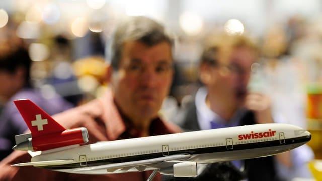 Ein kleines Flugzeug der Swissair steht auf einem Tisch, im Hintergrund sind in Unschärfe einige Menschen zu sehen.