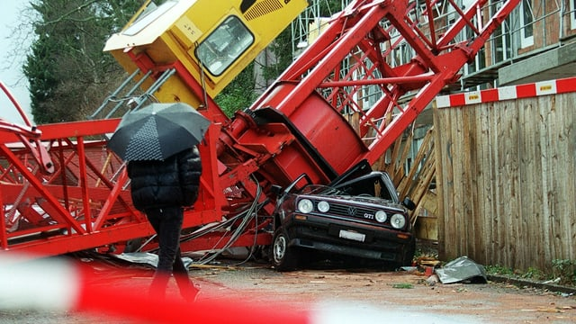Ein umgestürzter Baukran zerstört ein Auto total.