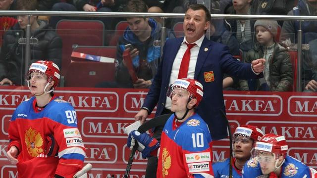 Russland-Coach Oleg Snarok an der bande. Vor ihm einige seiner Spieler.