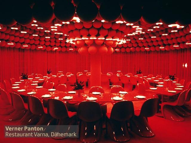 grosser runder roter Tisch mit weissen Tellern in komplett rotem Raum