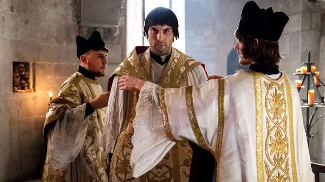 Zwingli im Priestergewand. Zwei Kollegen helfen ihm, die Stola zu richten.