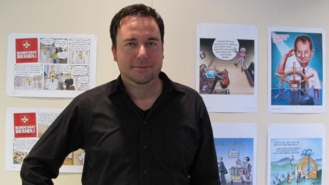 Marco Ratschiller steht vor einer Wand mit aufgehängten Karikaturen.