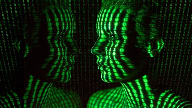 Auf einem weiblichen Kopf spiegeln sich grüne Ziffern.