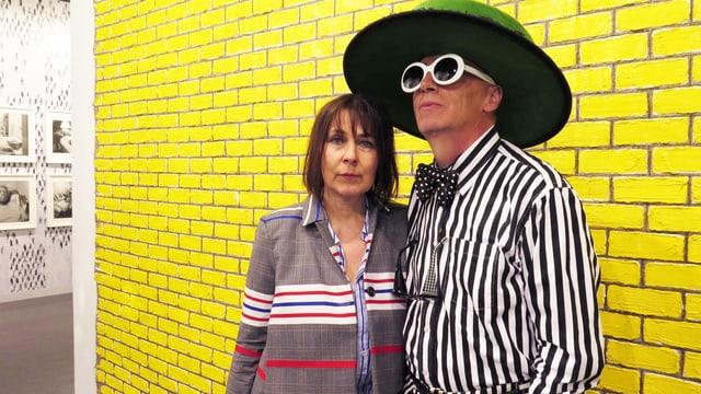 Ein Mann und eine Frau vor einer gelben Wand. Der Mann trägt einen grossen Hut und eine grosse Sonnenbrille.