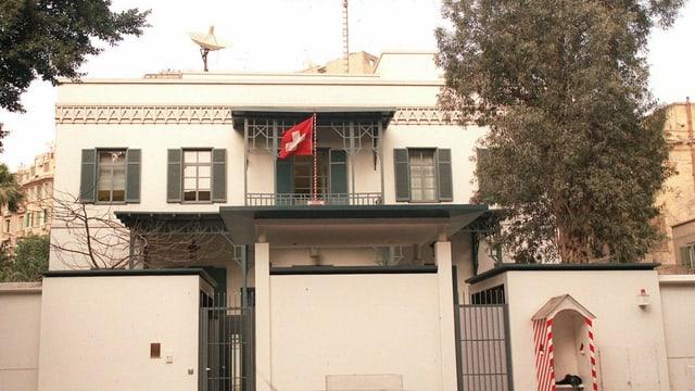 Front der Schweizer Botschaft in Kairo mit Schweizer Fahne und Satellitenschüssel auf dem Dach.