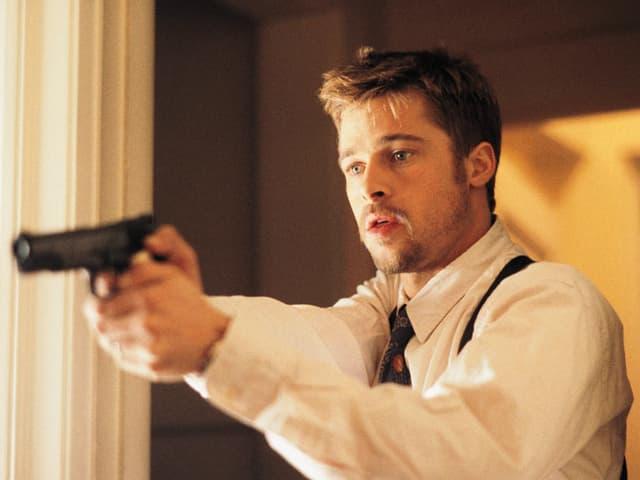 Brad Pitt hält eine Waffe in der Hand und zielt ins Ungewisse.