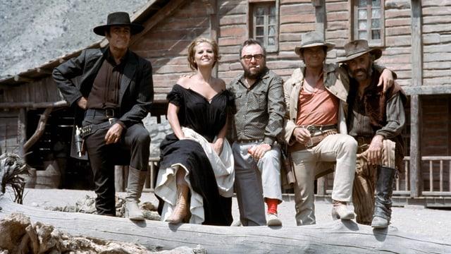 Vier Männer und eine Frau stehen in der Wüste vor einem Haus.