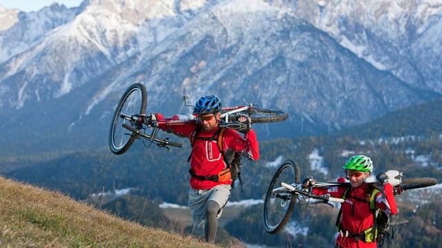 Zwei Mountainbiker tragen ihre Bikes den Berg hinauf