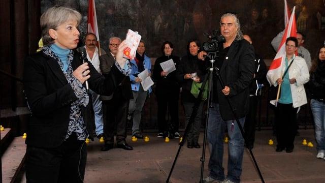 Brigitte Hollinger spricht an einer Protestaktion vor Journalisten
