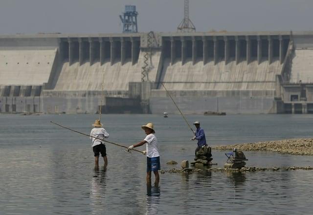 Drei Fischer fischen mit ihren Bambusruten vor dem grossen Staudamm.