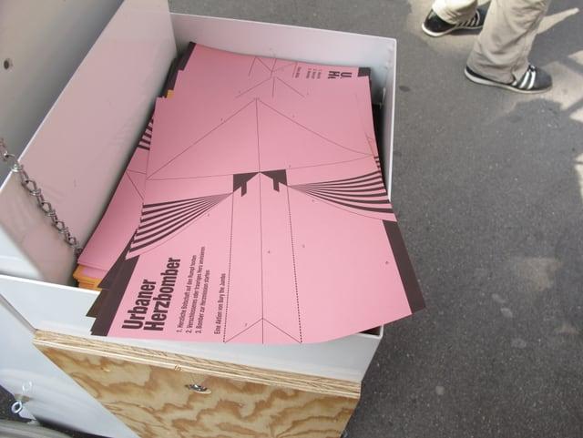 Eine Kiste mit rosa Blättern, darauf steht Urbaner Herzbomber.