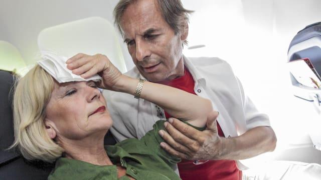 Eine Frau hält sich in einem Flugzeug sitzend ein feuchtes Tuch an die Stirn.