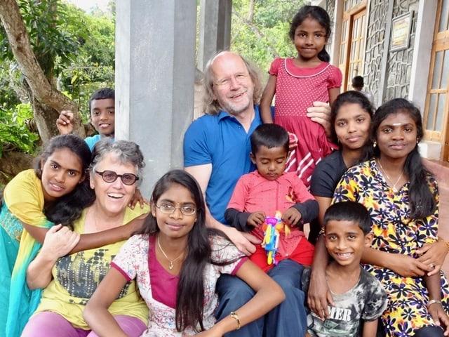 Weisser Mann und Frau inmitten Kinder aus Sri Lanka