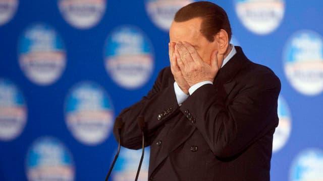 Berlusconi hält sich mit den Händen die Augen zu.