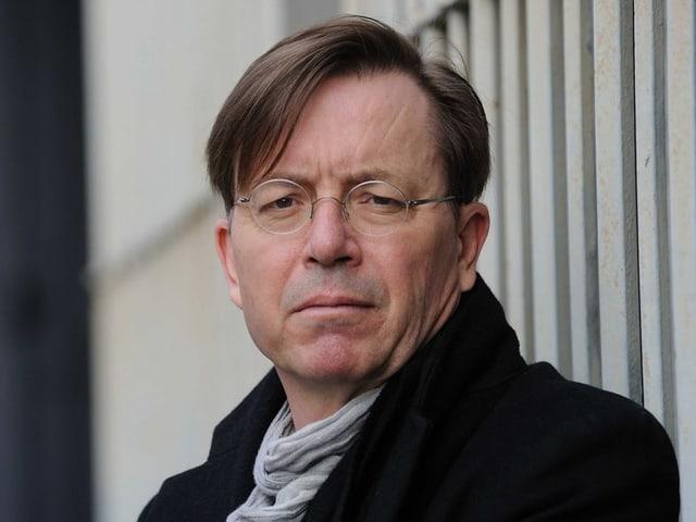 Ein Mann mit Brille und kurzem geradem Haar.